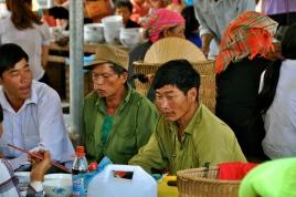 The men drink local corn liquor on market days