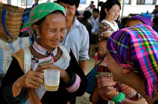 Flower Hmong woman doesn't like the taste of beer at Bac Ha Sunday market