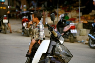 Young boy waiting for his mother at the market