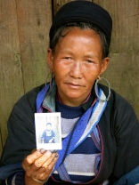 Black Hmong woman displaying her photo (fingernails dyed blue from working with indigo)