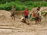 Kids playing on the shore outside a village along the Nam Ou River