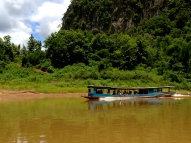 A similar boat going the opposite direction down the Nam Ou River