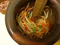mashing papaya salad with a mortar and pestle